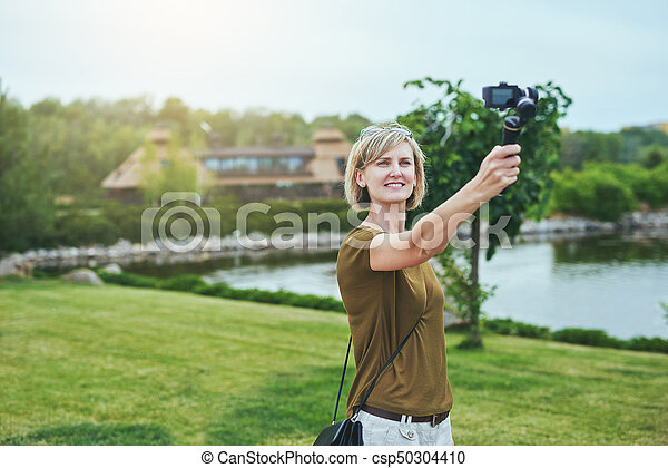 Woman capturing herself with personal camera - csp50304410