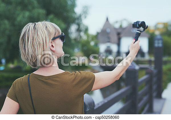 Woman capturing herself with personal camera - csp50258060