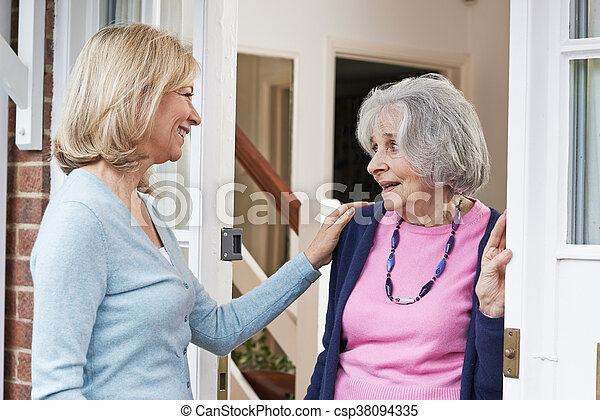 Woman Checking On Elderly Female Neighbor - csp38094335