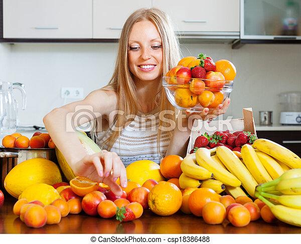woman choosing fruits in home kitchen - csp18386488