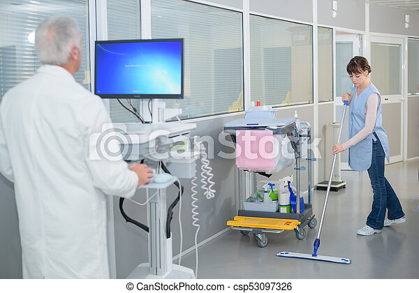 Woman cleaning hospital corridor, doctor using computer - csp53097326