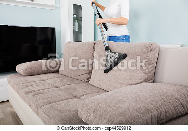 Woman Cleaning Sofa With Vacuum Cleaner   Csp44529912