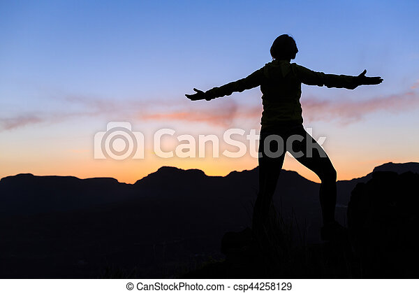 Woman climbing success silhouette in mountains sunset - csp44258129