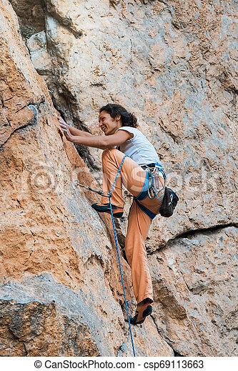 Woman climbs mountain. - csp69113663