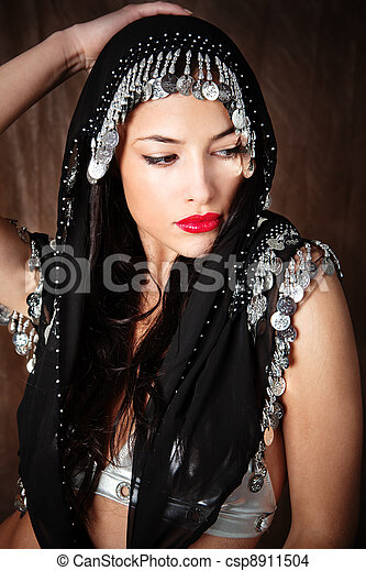 woman covered with black scarf holding hand on her head - csp8911504