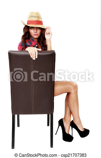 woman cowgirl sitting on a chair isolated on white - csp21707383