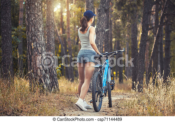 woman cyclist riding mountain bike in the forest - csp71144489