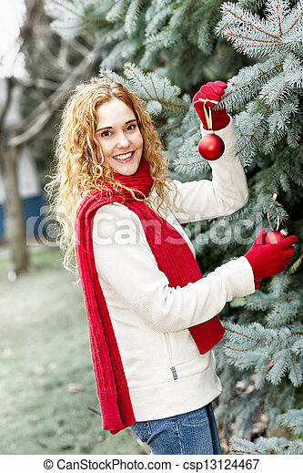 Decorating Christmas Trees Outside.Woman Decorating Christmas Tree Outside