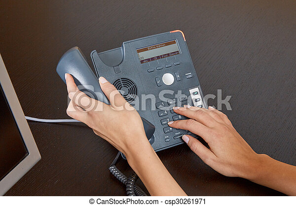 Woman dialing on a telephone - csp30261971