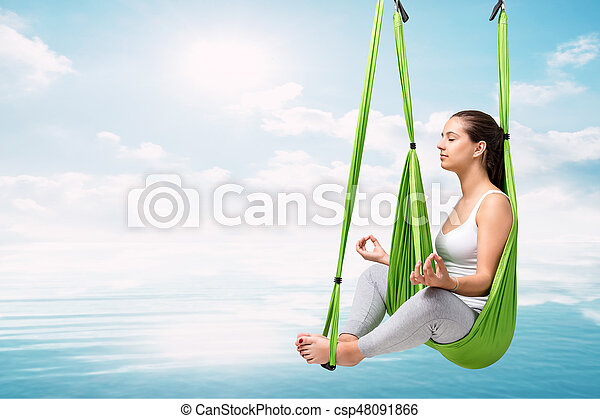 Woman doing aerial antigravity yoga over lake. - csp48091866