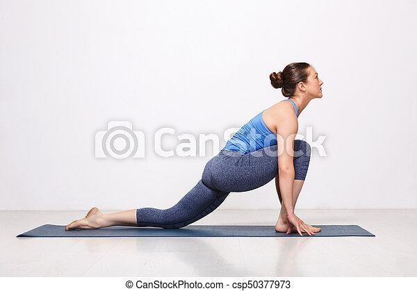 woman doing hatha yoga asana anjaneyasana  low crescent