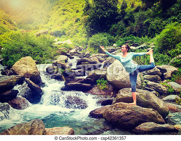 woman doing yoga asana natarajasana outdoors at waterfall