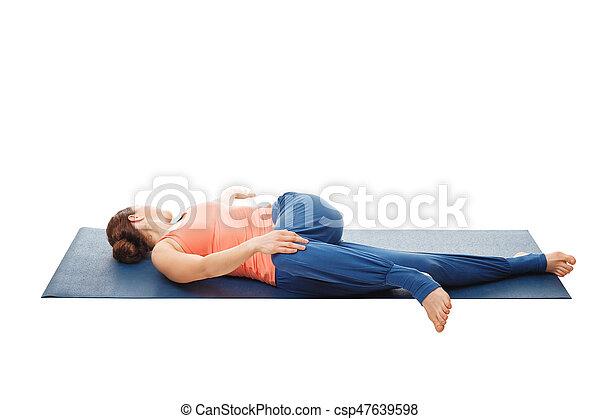 woman doing yoga asana parivrtta ardha pawanmuktasana