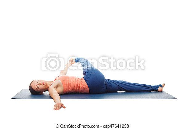 woman doing yoga asana revolved kneetochest pose