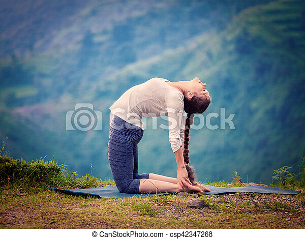 woman doing yoga asana ustrasana camel pose outdoors yoga