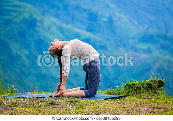 woman doing yoga asana ustrasana camel pose outdoors yoga