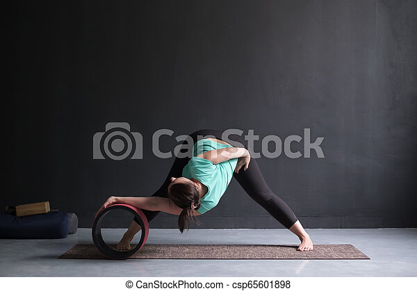 woman doing yoga asana wide legged forward bend using