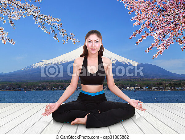 woman doing yoga exercise on wood floor with Mt Fuji and Cherry Blossom - csp31305882