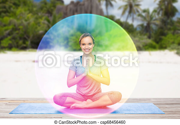 woman doing yoga in lotus pose with rainbow aura