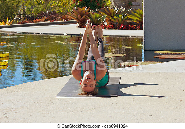 woman doing yoga outdoors in fish pose an athletic brown