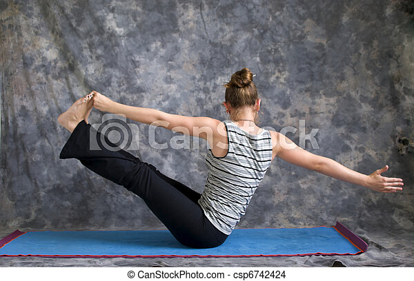 young woman on yoga mat in woman doing yoga posture