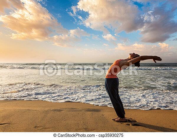 woman doing yoga sun salutation surya namaskar young