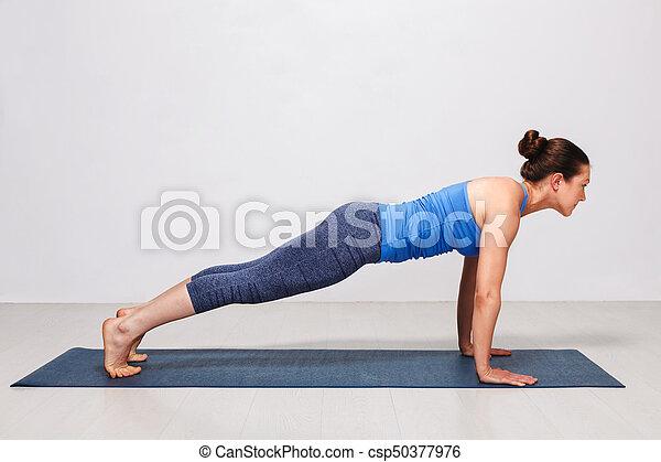woman doing yoga surya namaskar sun salutation asana