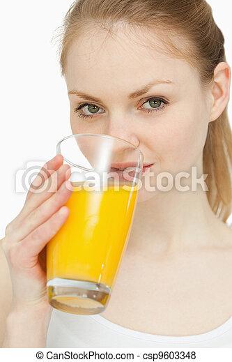 Woman drinking a glass of orange juice - csp9603348