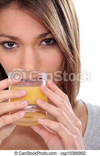 Woman drinking a glass of orange juice - csp10386902