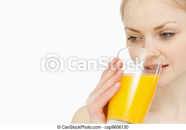 Woman drinking a glass of orange juice while looking away - csp9606130