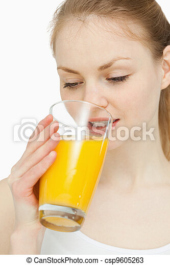 Woman drinking a glass of orange juice while looking at it - csp9605263