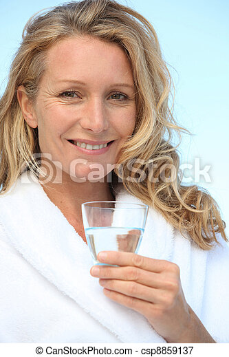 Woman drinking a glass of water in a bathrobe - csp8859137
