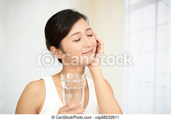 Woman drinking a glass of water - csp68232611