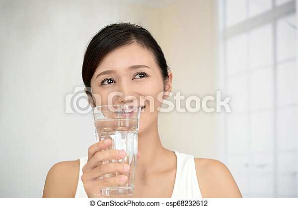 Woman drinking a glass of water - csp68232612