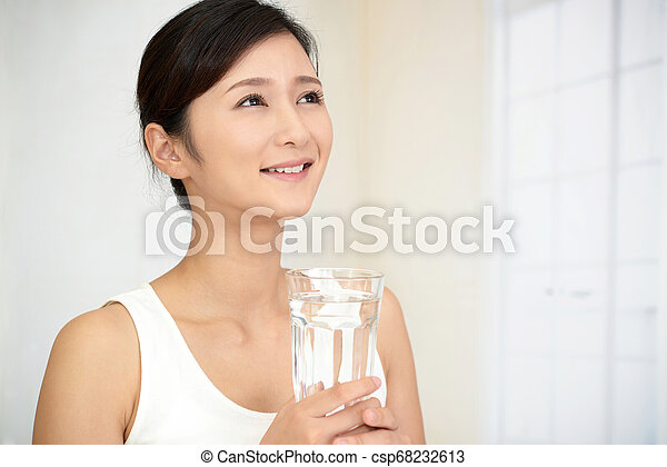 Woman drinking a glass of water - csp68232613