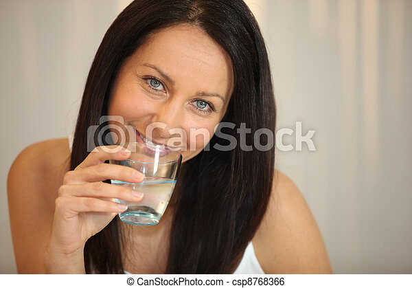 Woman drinking a glass of water - csp8768366