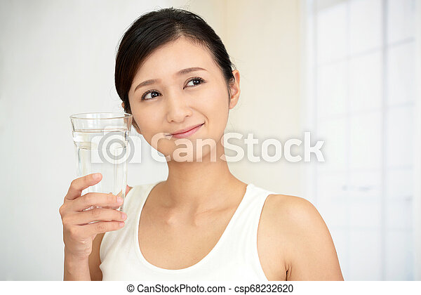 Woman drinking a glass of water - csp68232620