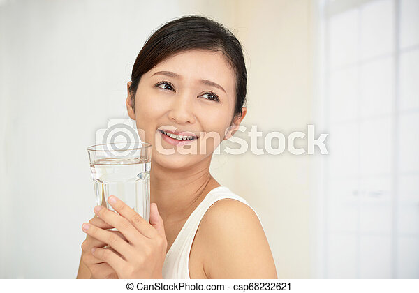 Woman drinking a glass of water - csp68232621