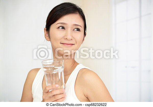 Woman drinking a glass of water - csp68232622