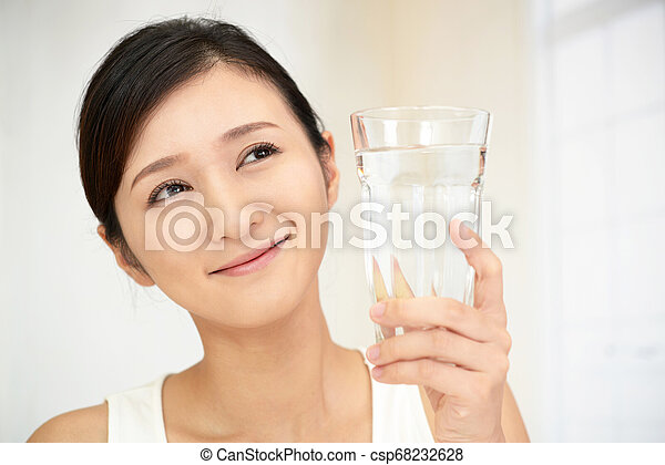 Woman drinking a glass of water - csp68232628