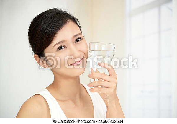 Woman drinking a glass of water - csp68232604