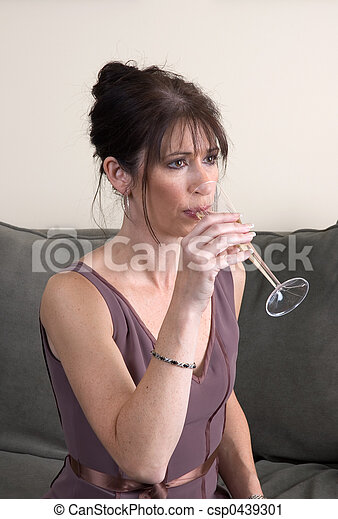 Woman Drinking Champagne on Couch Alone - csp0439301