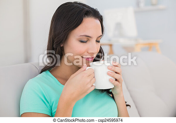 Woman drinking coffee on couch - csp24595974