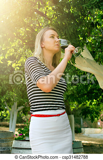Woman drinking glass of red wine at the winery. - csp31482788