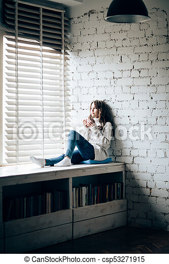 Woman drinking hot coffee sitting on window sill at home - csp53271915