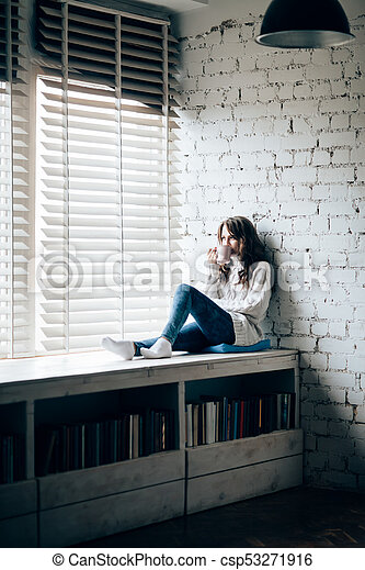 Woman drinking hot coffee sitting on window sill at home - csp53271916
