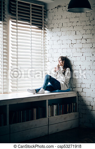 Woman drinking hot coffee sitting on window sill at home - csp53271918