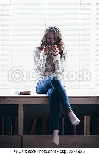 Woman drinking hot coffee sitting on window sill at home - csp53271926