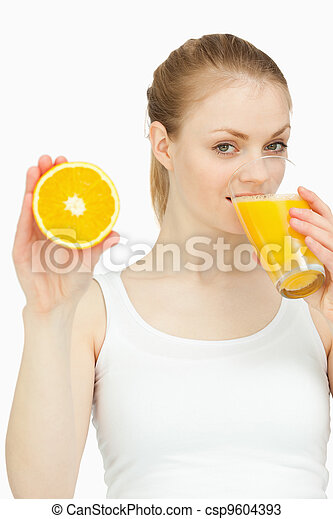 Woman drinking in a glass while presenting an orange - csp9604393