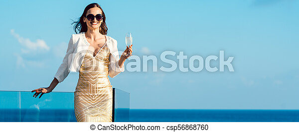 Woman drinking sparkling wine looking over ocean - csp56868760